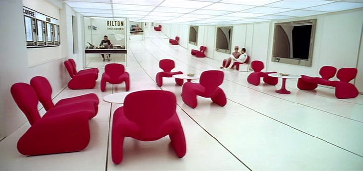 Futuristic furniture: sleek white floors and ceilings, contrasting with scarlet Koonsian chairs in 2001: A Space Odyssey.