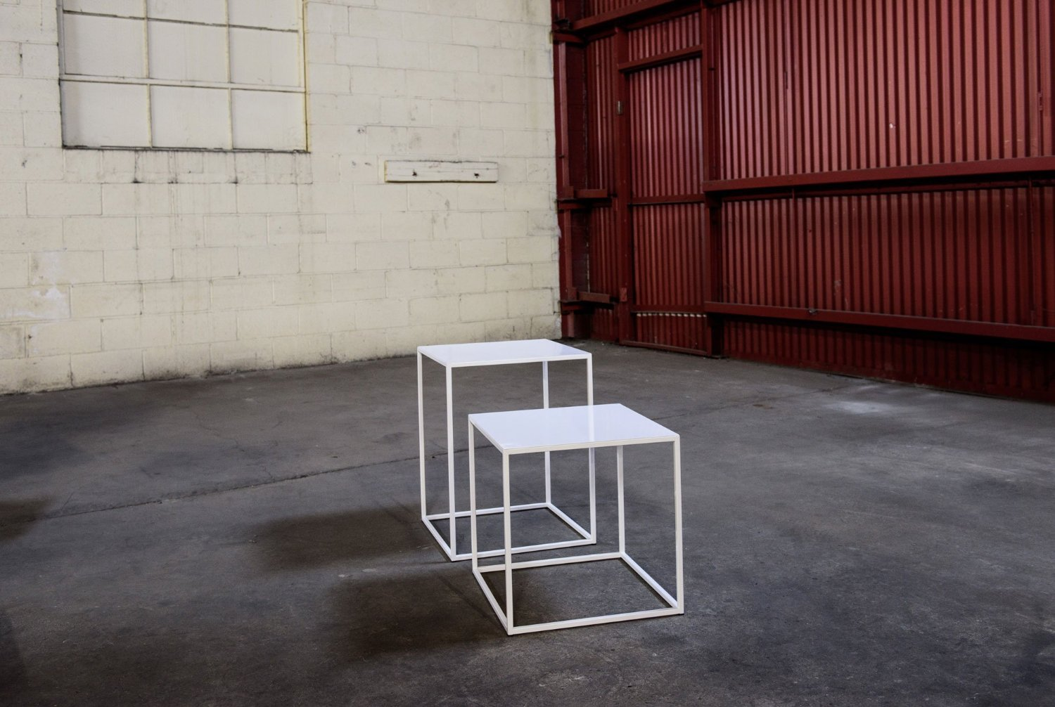 Two powder-coated white end tables, examples of futuristic furniture, by Patrick Cain Designs.