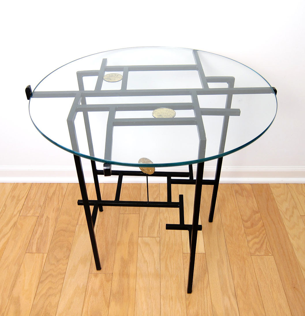 Black-painted steel end table with a glass top, sold by Etsy shop ObjectOfBeauty.