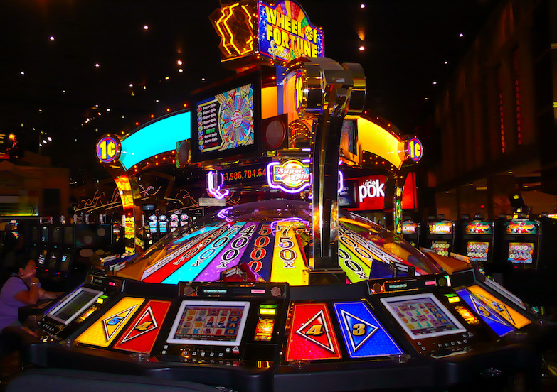 Bright neon Wheel of Fortune machine in a casino. Photo by La super Lili.